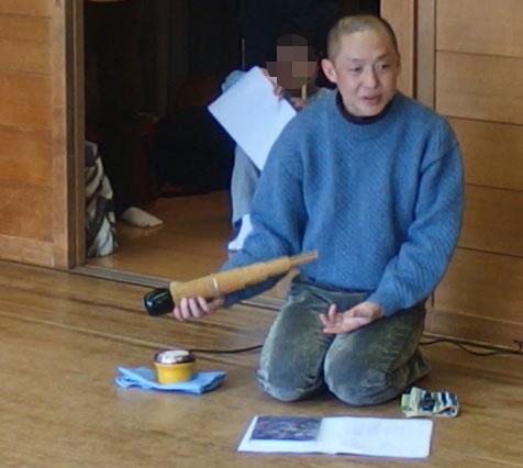 笙(しょう)を暖める石川高先生。