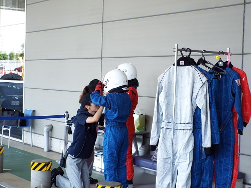 待機場所で服の上からレーシングスーツを着る。